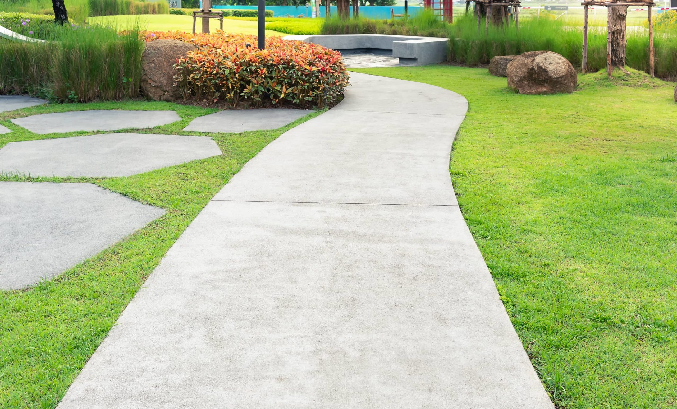 This is a picture of a concrete walkway with some decorative concrete paths and concrete bench in a garden.
