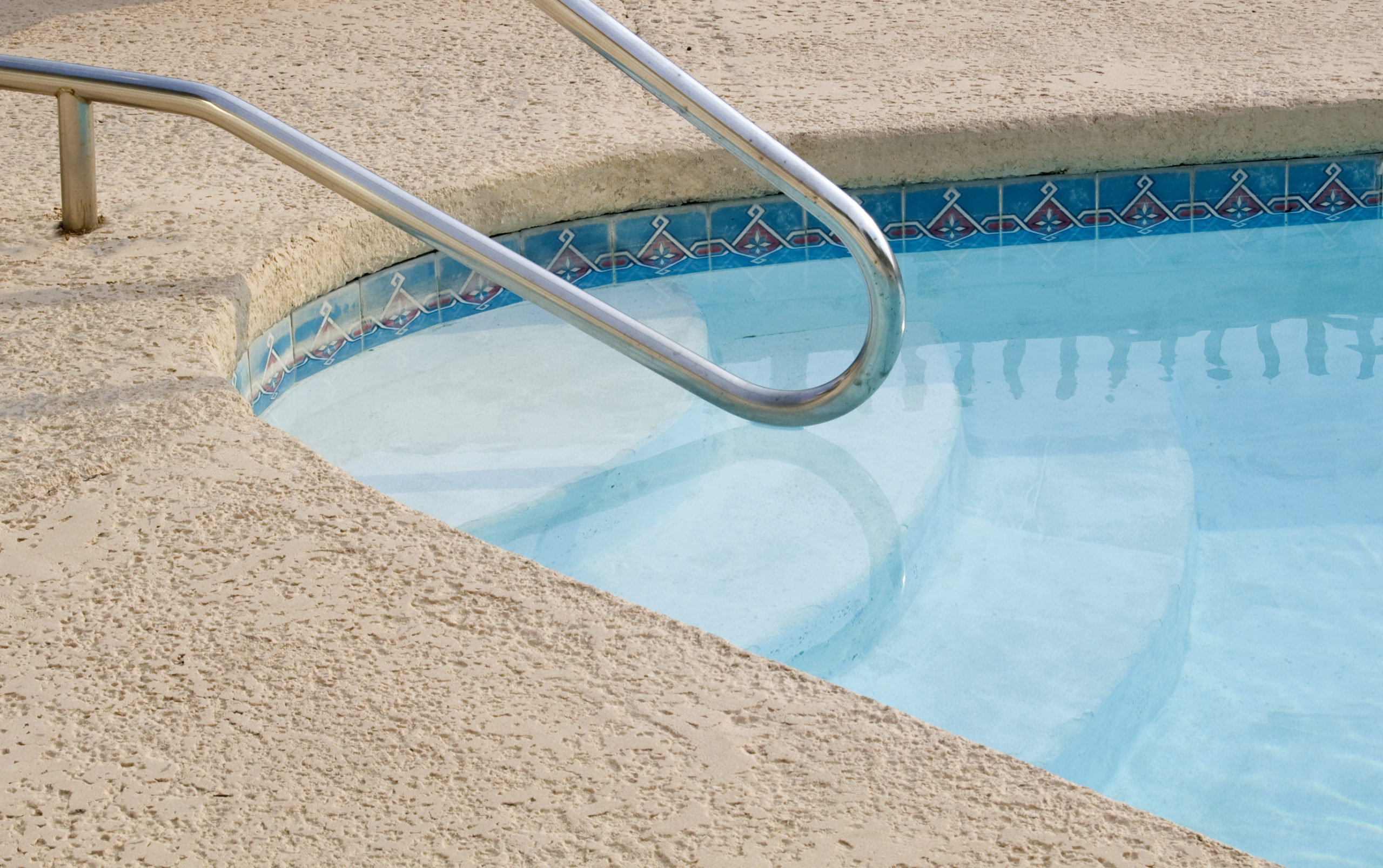 This is an image of a pool with a pool ladder and concrete deck.