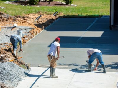 This is an image of contractors smoothing out a freshly made concrete driveway.